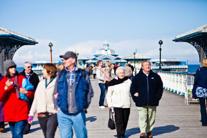 Llandudno pier engagement shoot, couple amongst crowd