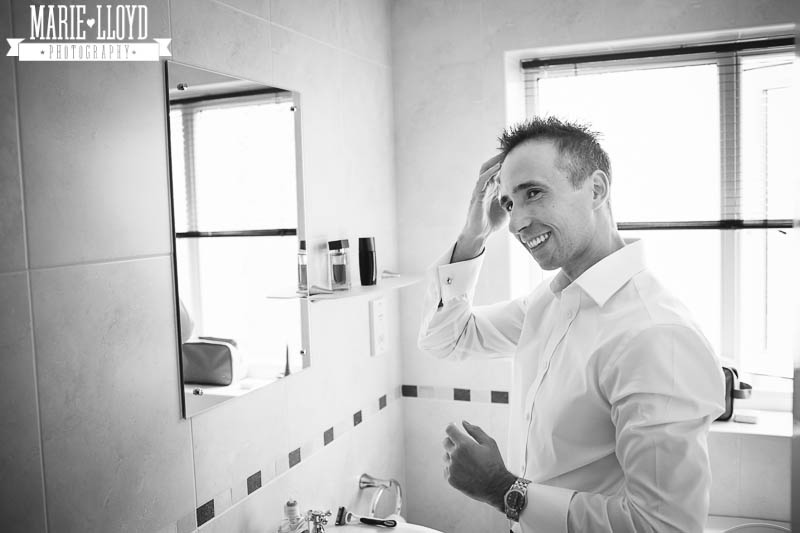 Black and white wedding prep shot of the groom applying gel to his hair