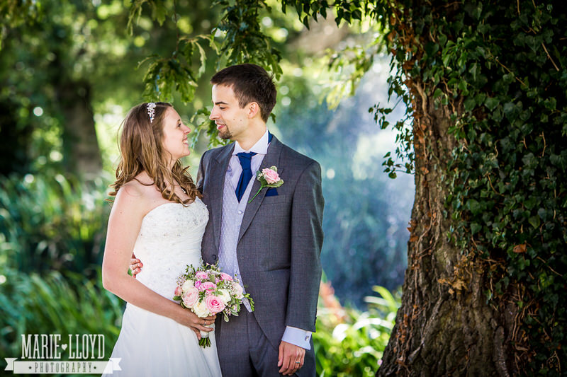 Bride and groom portrait under a tree looking towards each other