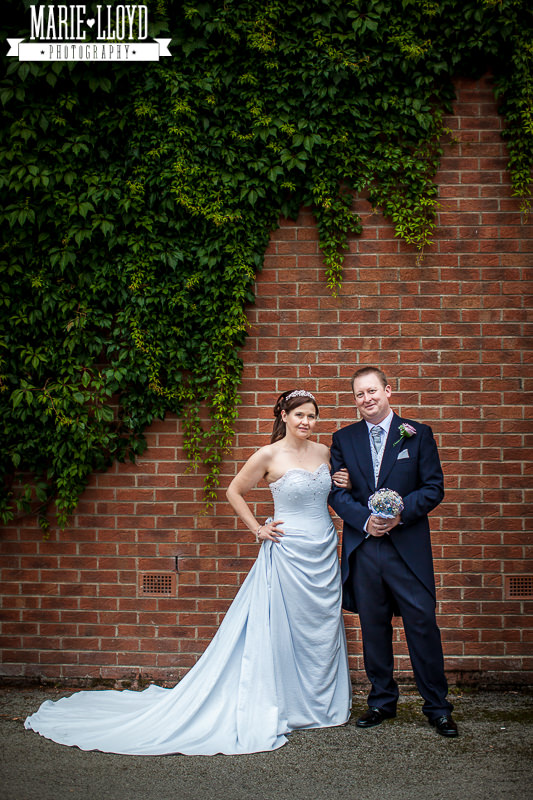Bride and groom portrait under the ivy against a brick wall.