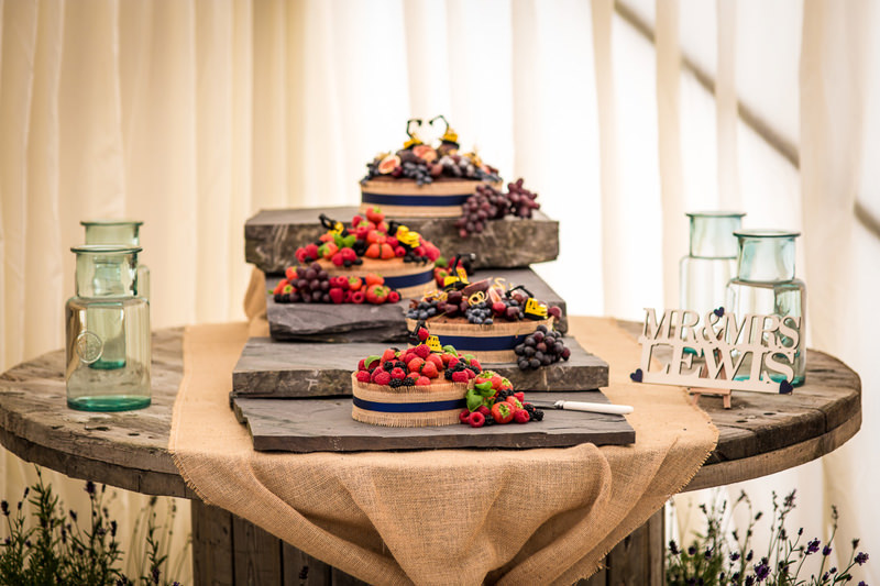 Amazing multiple tier wedding cake with fruit toppings and JCB themed decoration