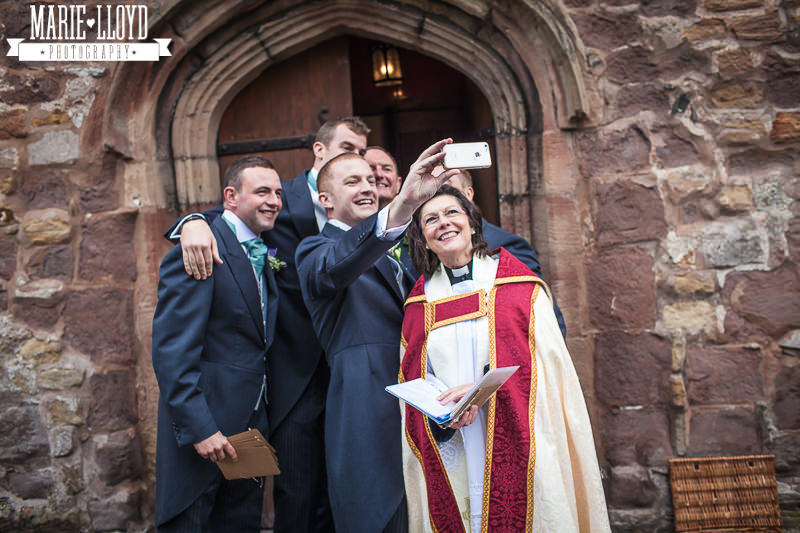 Groomsmen taking a selfie with the vicar at St Asaph church