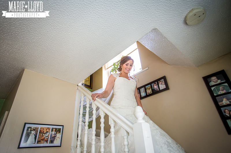 Bride coming down the stairs at her home, ready for the wedding