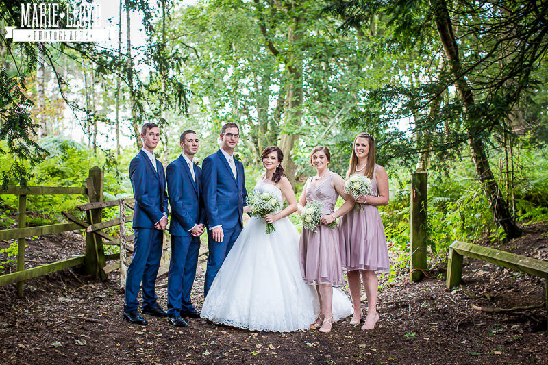 Peckforton Castle wedding group shot in the trees outside the gate