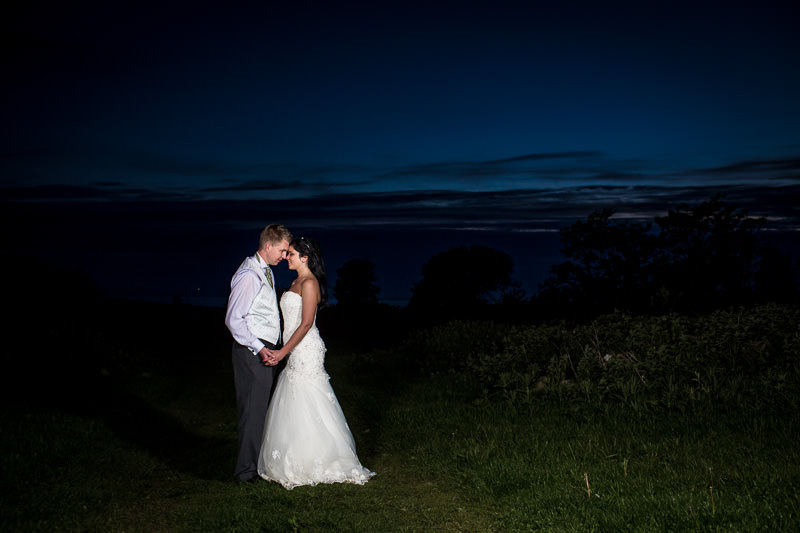 Bride and groom photograph under a moonlit sky