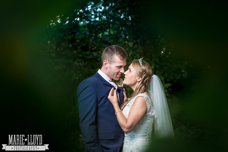 Liverpool bride and groom portrait through the foliage of a tree at the edge of the Huyton GOlf Course by Marie Lloyd