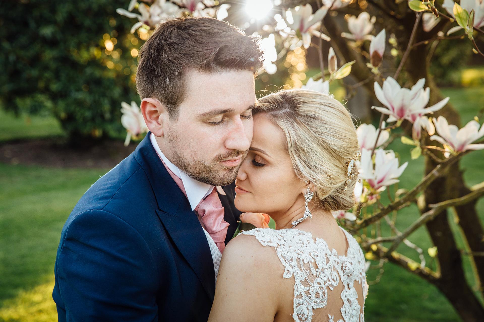 Wedding couple hugging under blossom tree at Colshaw Hall