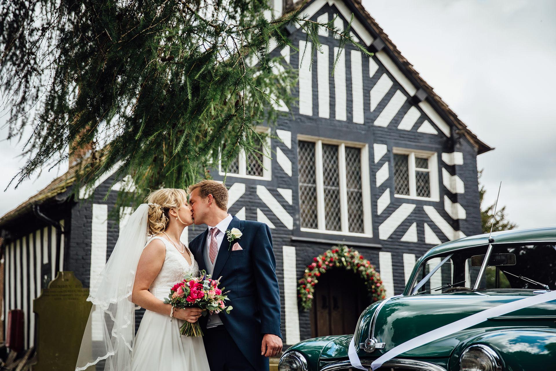 Wedding couple kissing outside church