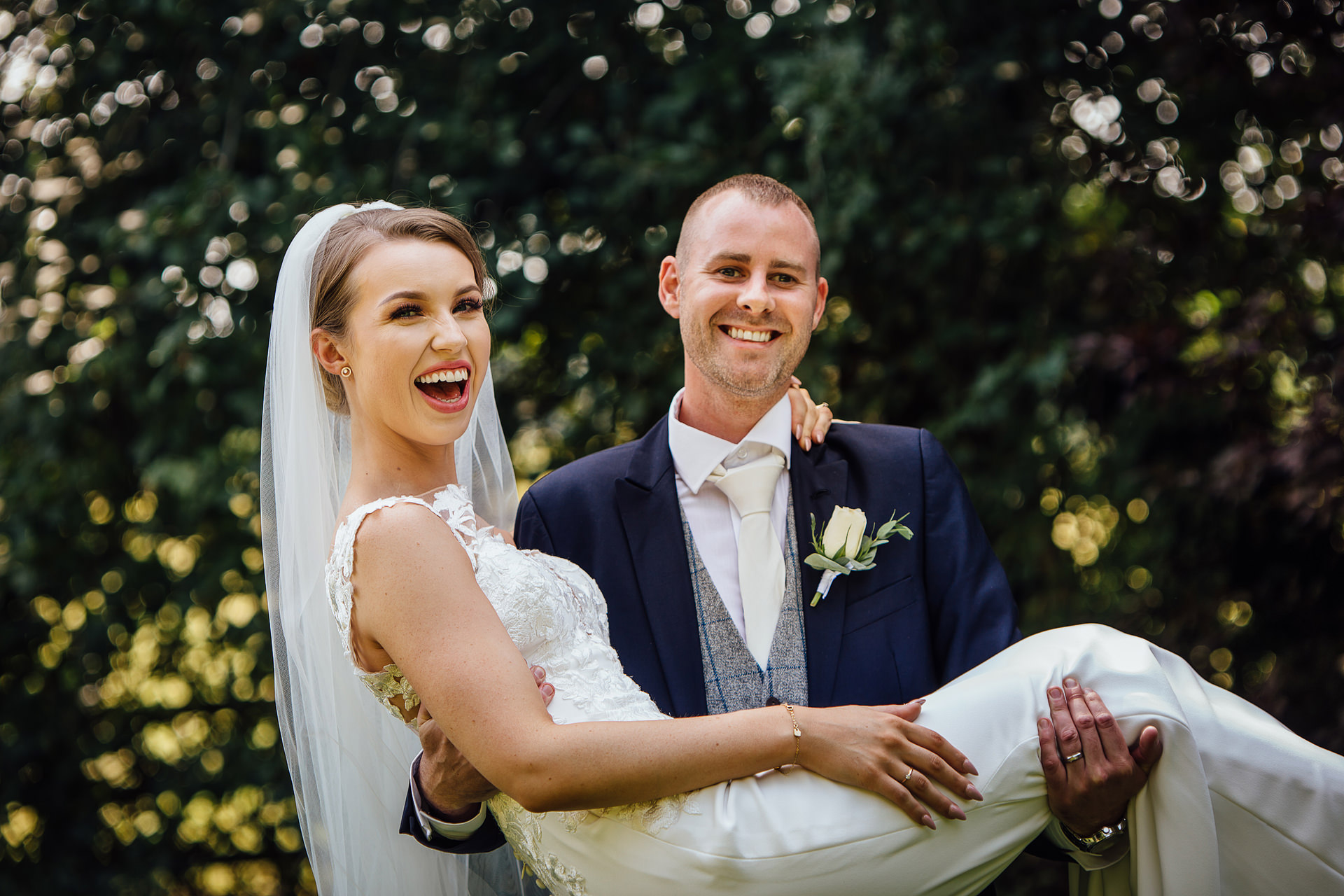Groom carrying bride at mitton hall, clitheroe
