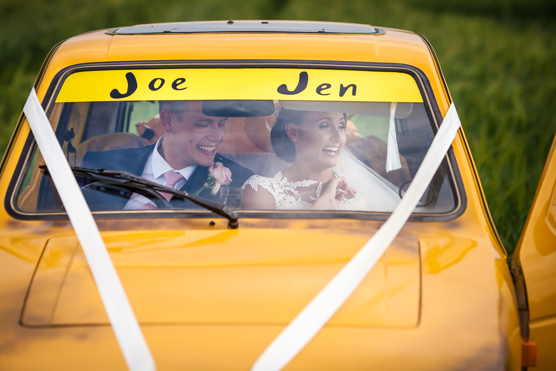 bride and grrom in delboy style car