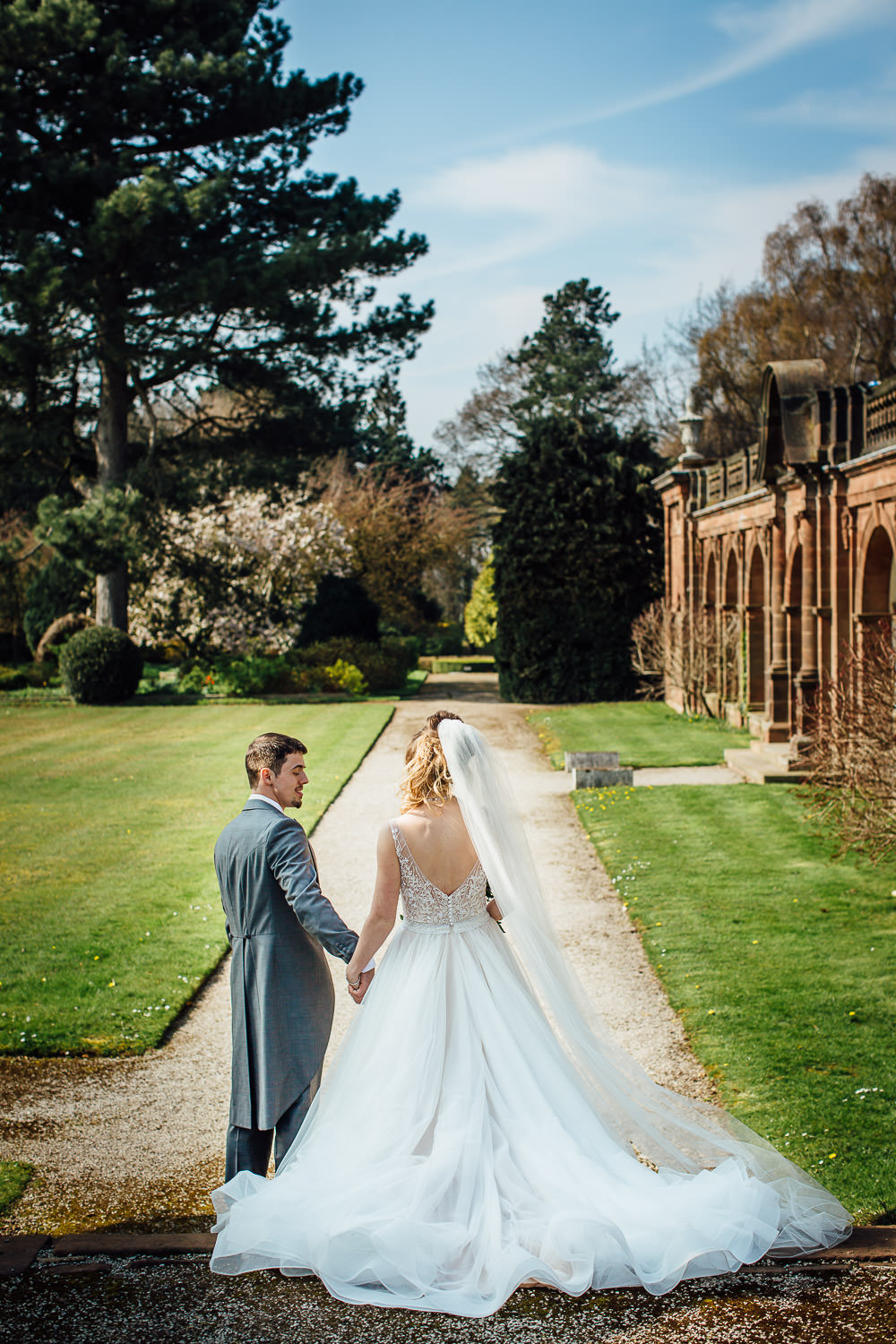 Bride and Groom walking through gardens of Thornton Manor in the Wirral