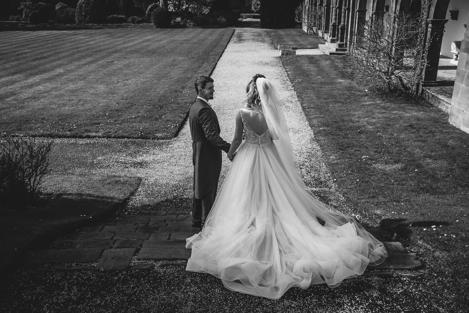 Bride and Groom in black and white walking through gardens of the Thornton Manor in the Wirral