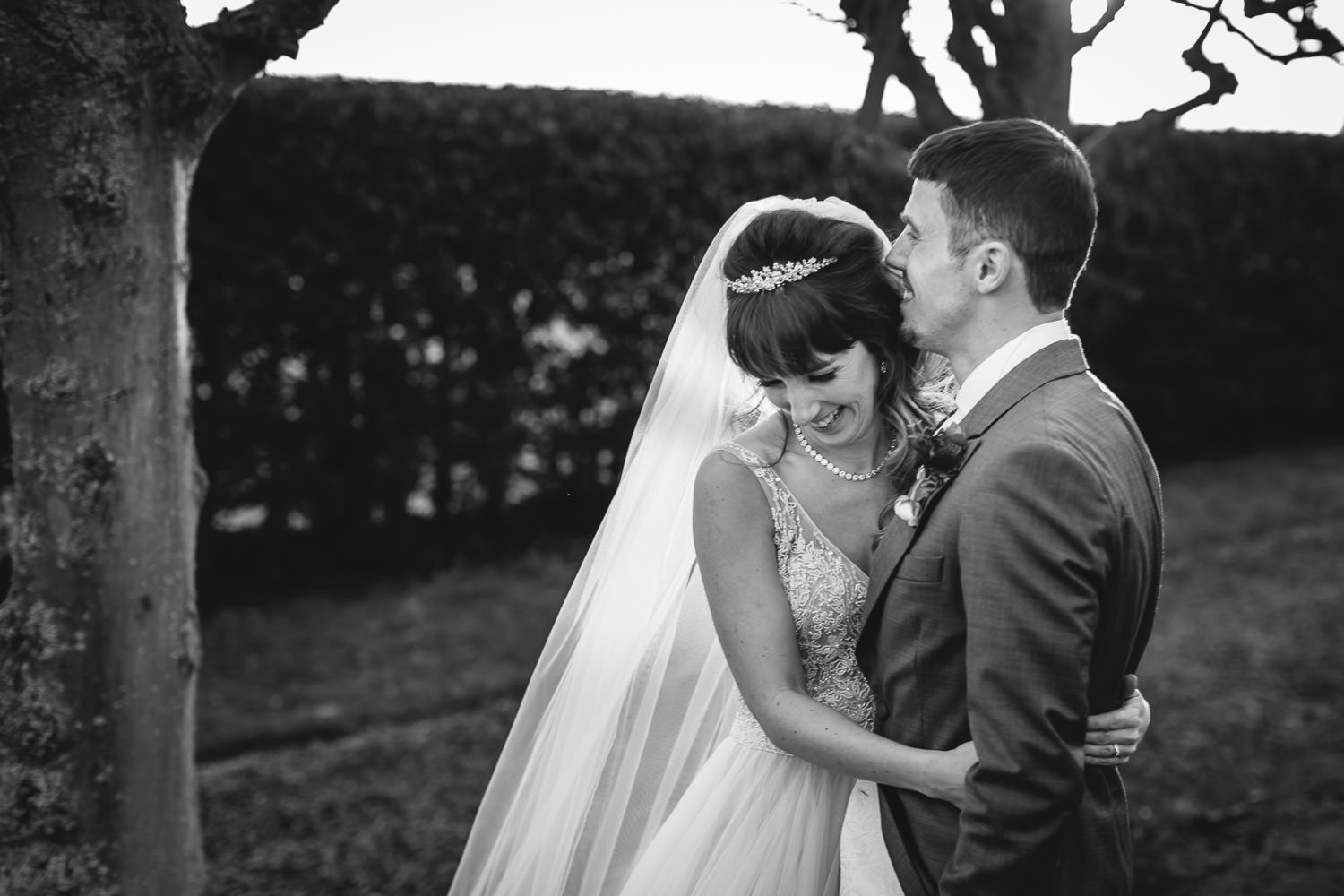 Wedding couple laughing in the tree lined path at thornton manor