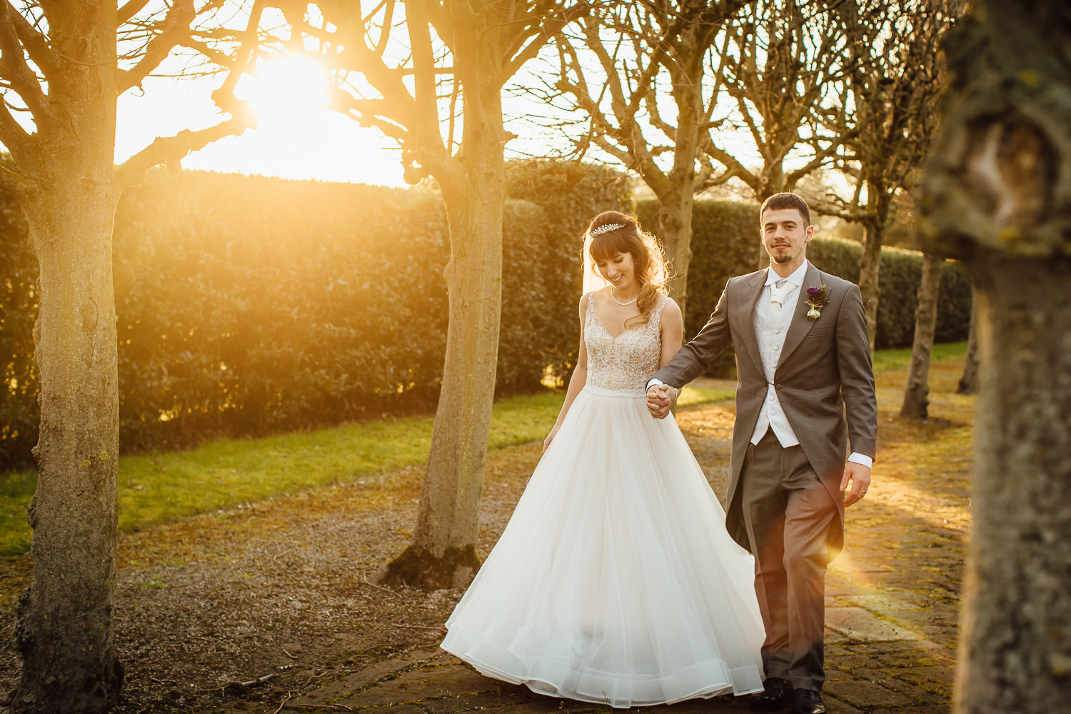 Sunsetting on wedding couple walking through tree lined path in Thornton Manor