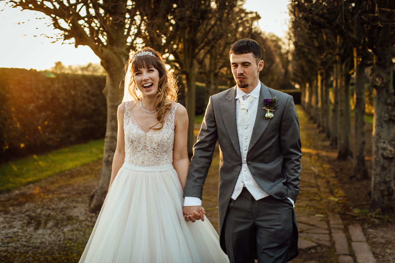 Wedding couple laughing on tree lined walk in Thornton Manor