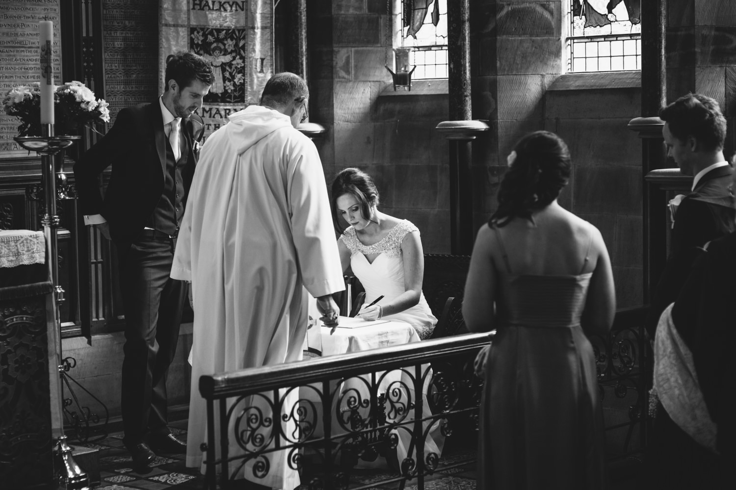 Wedding Photography of the couple signing the register in a church in  North Wales