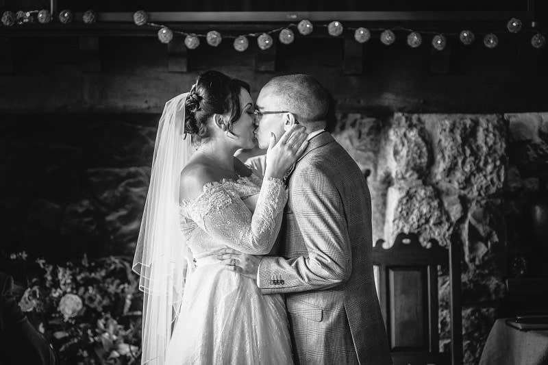 black and white first kiss of wedding ceremony in North Wales, wedding photography example